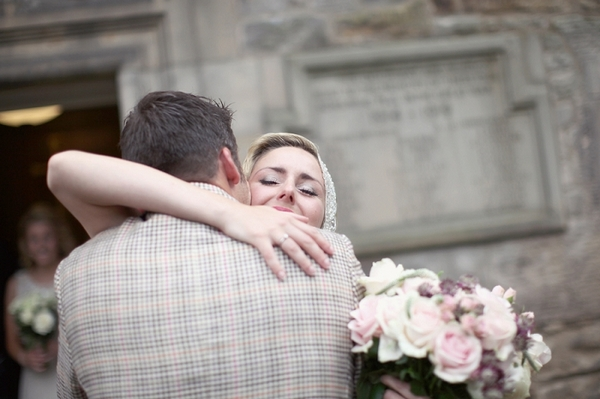 Bride and groom hug outside church