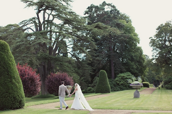 Bride and groom walking through Kirknewton Stables' grounds