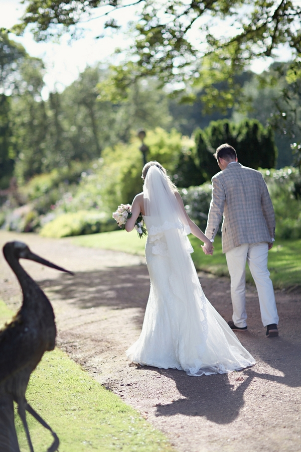 Bride and groom walking in gardens of Kirknewton Stables