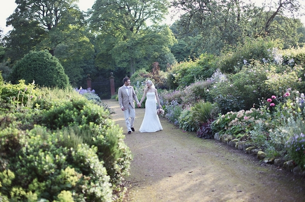 Bride and groom walking though Kirknewton Stables' gardens