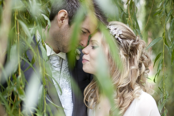 Picture of bride and groom taken though tree brancges - Picture by Daniel Hough Photography