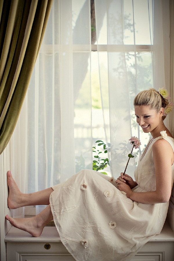 Bride with graceful updo sitting on window ledge
