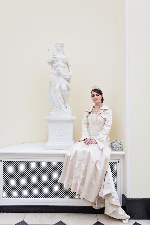 Bride sitting next to statue