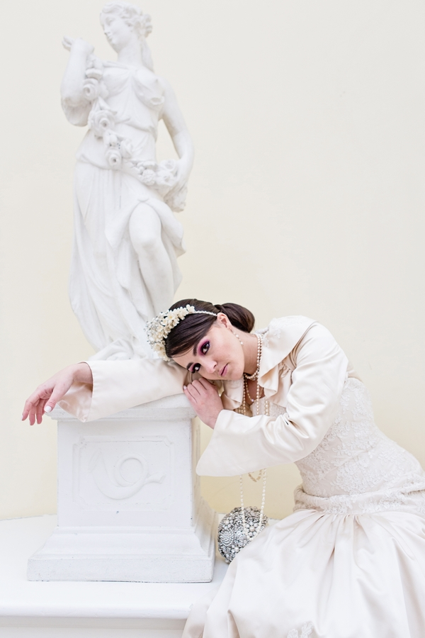 Bride leaning on statue
