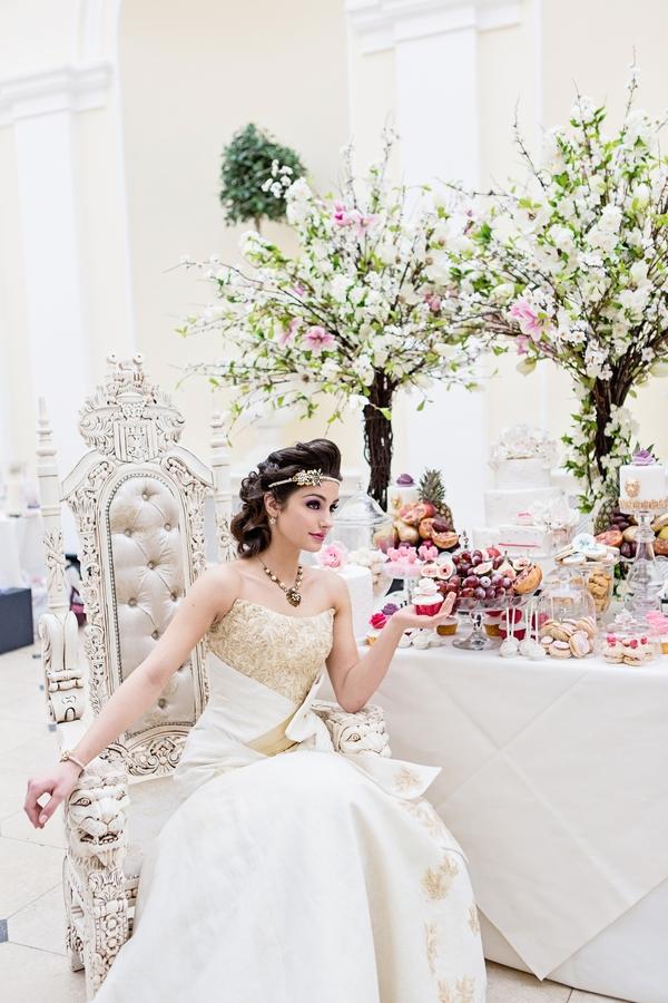 Bride sitting next to wedding cake table