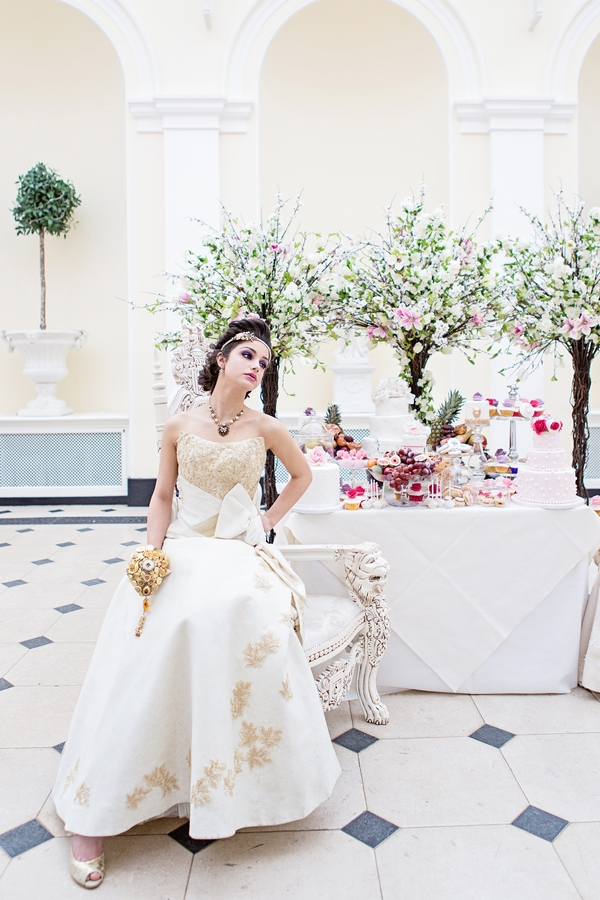 Bride sitting next to cake table