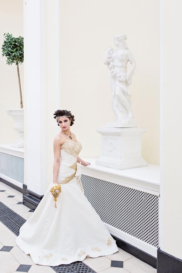 Bride standing next to statue