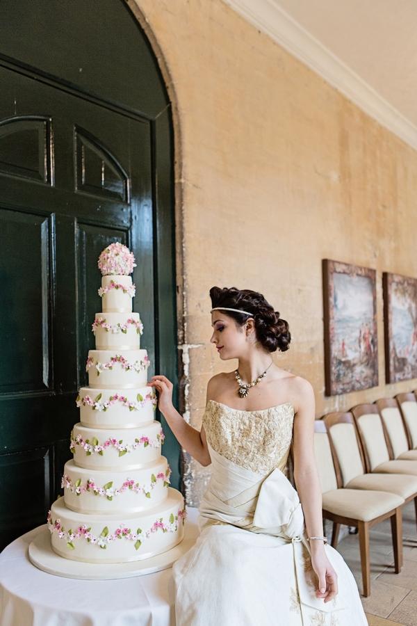 Bride next to tall wedding cake
