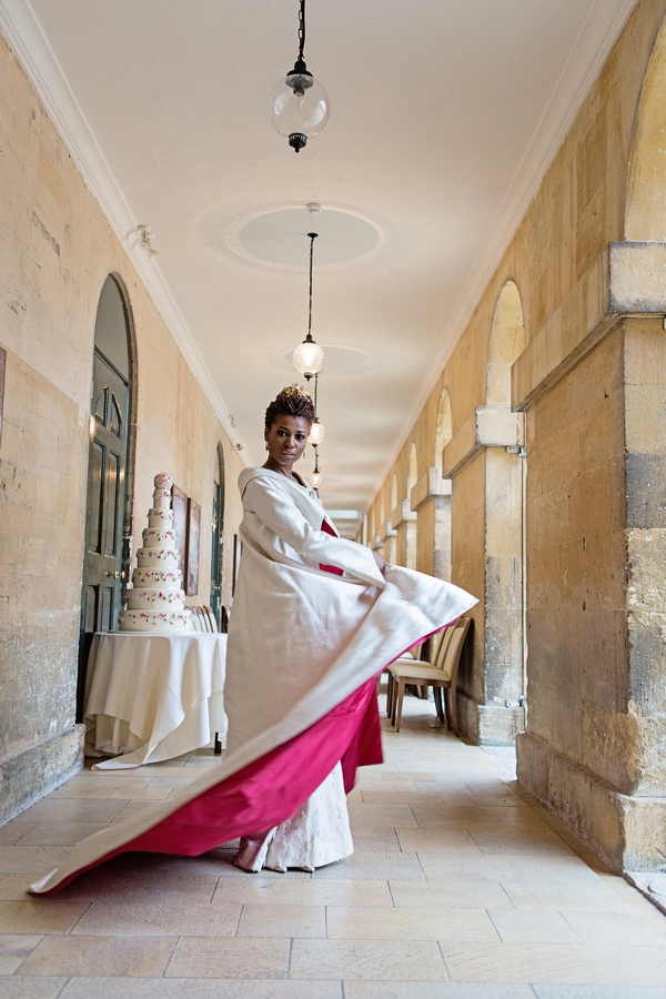 Bride twirling in red-lined long wedding coat