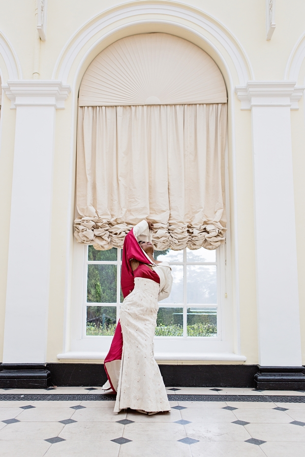 Bride with red-lined long wedding coat standing in front of window