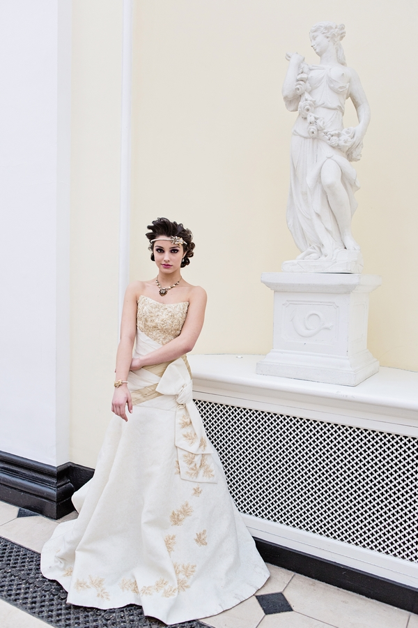 Bride standing by statue