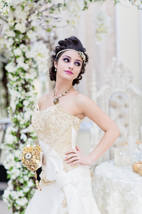 Bride holding gold brooch bouquet