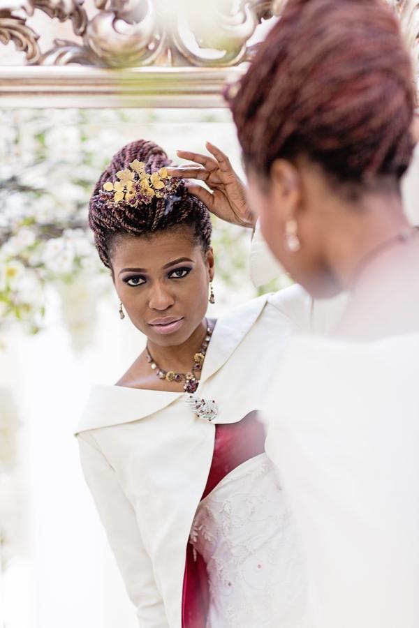Bride adjusting headpiece in mirror