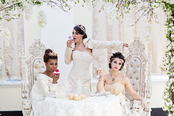 Brides sitting at table with cakes