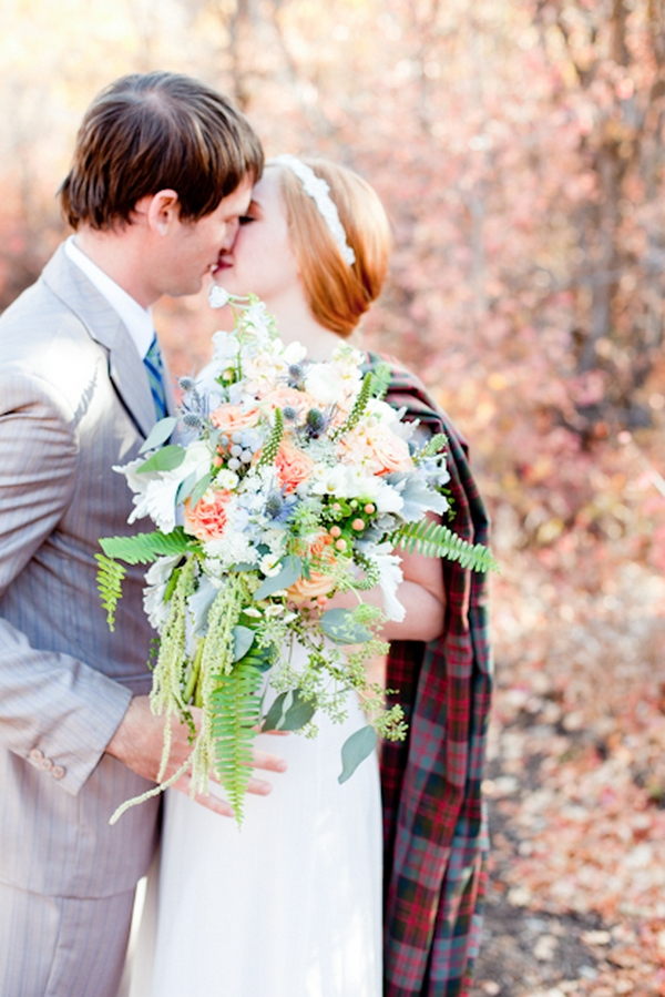 Bride and groom kiss in front of bouquet