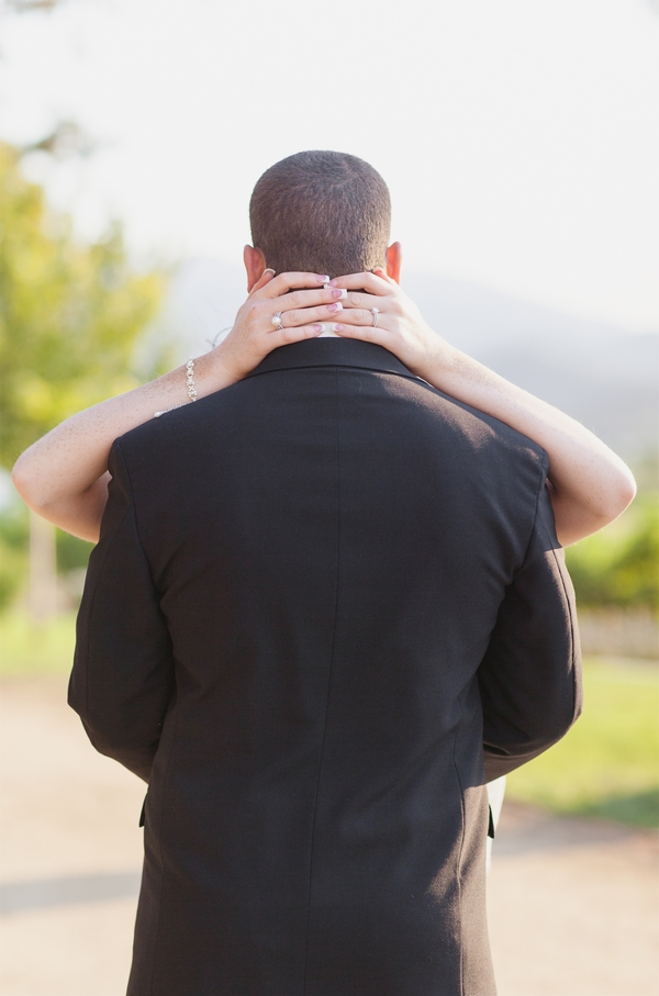Back of groom with bride's hands around back of neck