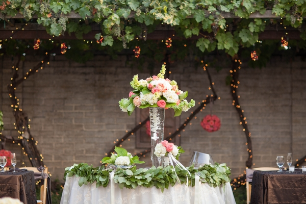 Table with tall vase of wedding flowers