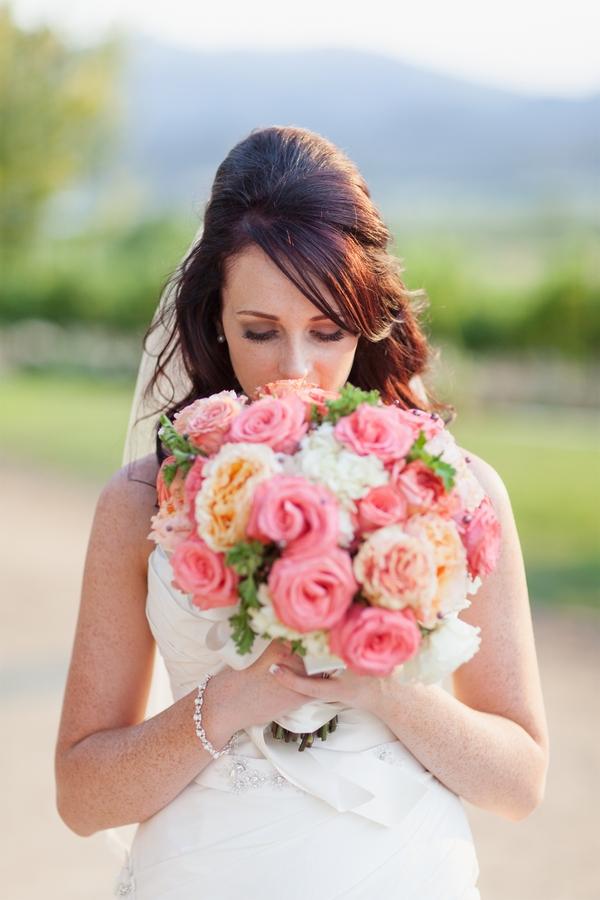 Bride smelling flowers in bouquet