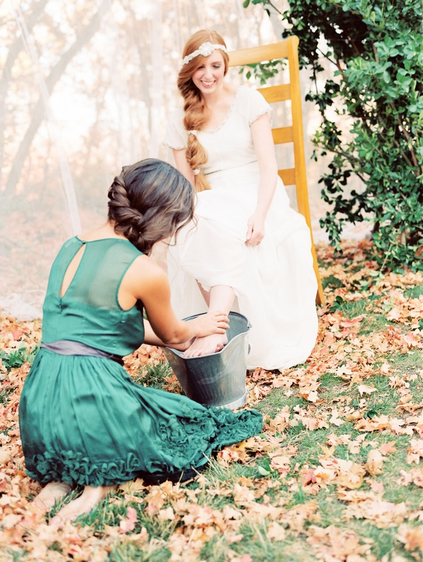 Bridesmaid washing bride's feet