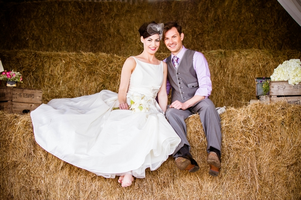 Vintage bride and groom sitting on hay bales