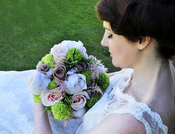 Bride sitting looking at bouquet