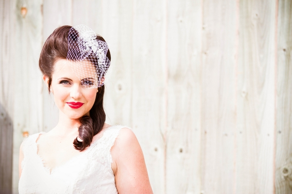 Vintage bride with birdcage veil in front of white fence