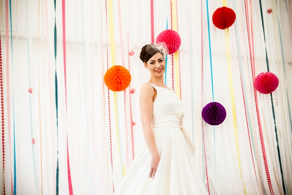 Bride in front of coloured streamers and pom poms