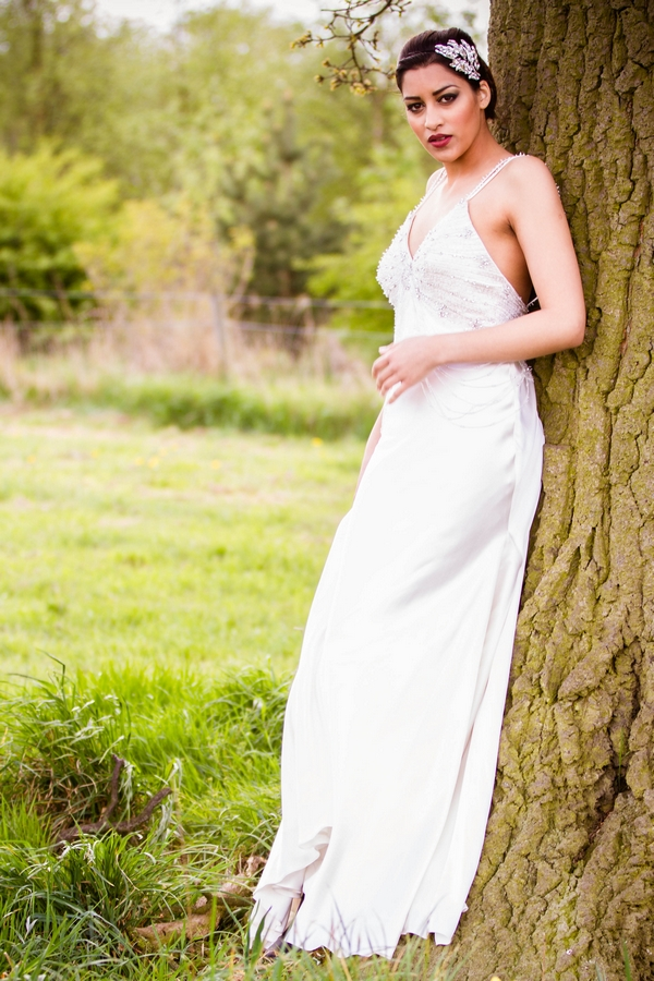 Bride leaning on tree