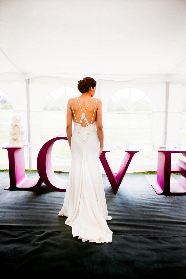 Bride standing in front of large purple LOVE letters