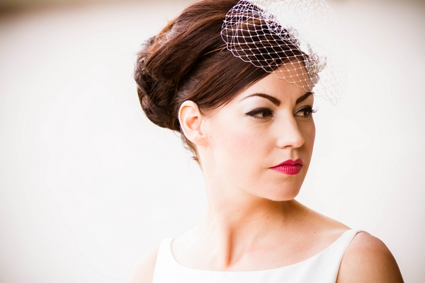 Bride wearing birdcage fascinator