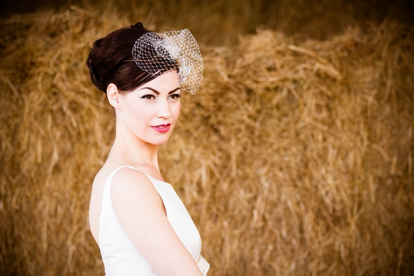 Vinatge bride standing in front of hay