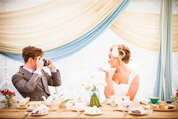 Groom taking picture of bride blowing kiss