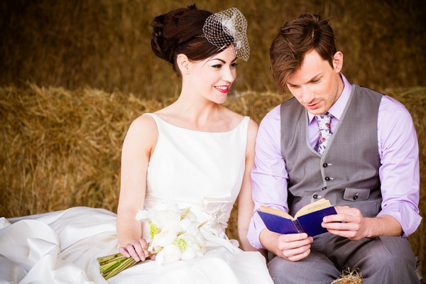 Bride and groom on hay bales reading a book