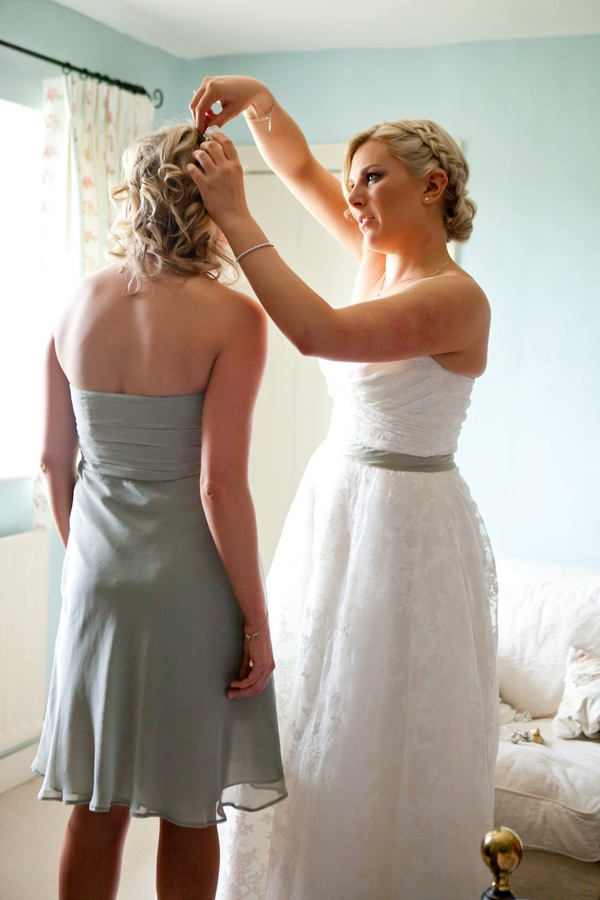 Bride helping bridesmaid with hair