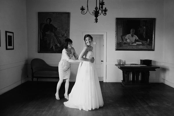 Bride having back of wedding dress done up