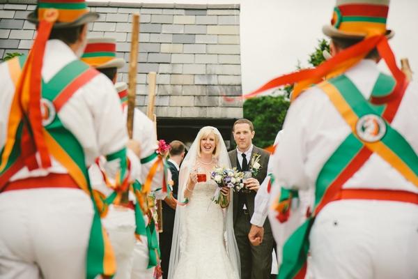 Bride and groom walking past Morris Dancers