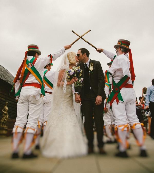 Bride and groom kiss under Morris Dancers' guard of honour