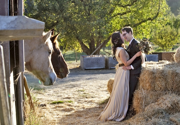 Bride and groom leaning on hay bales