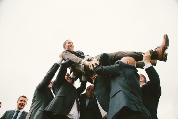 Groomsmen carrying groom