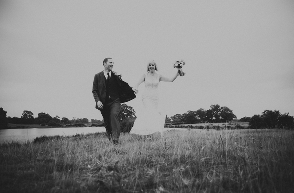 Bride and groom walking across field