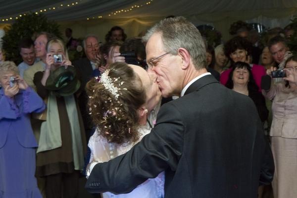 Bride and groom kiss on dancefloor