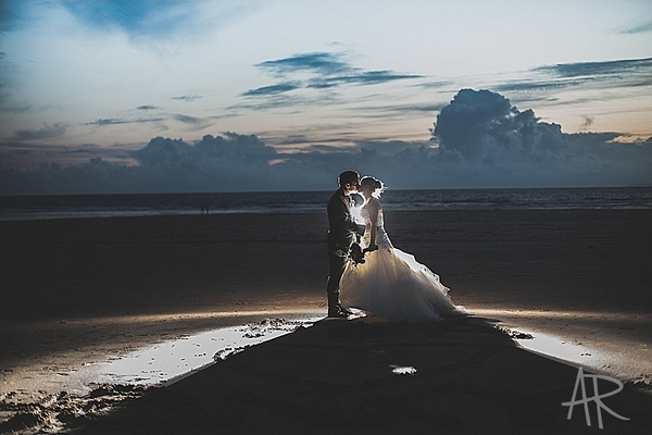 Bride and groom on beach with light shining behind them - Picture by Ayesha Rahman Photography