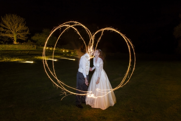 Bride and groom kssing behind heart made with sparkler