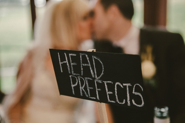 Bride and groom kissing behind Head Prefects wedding table sign