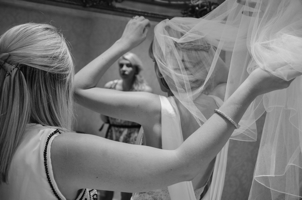 Bride putting on veil