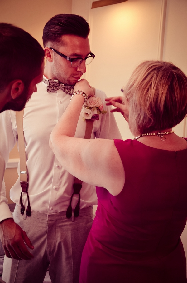 Lady putting on groom's buttonhole