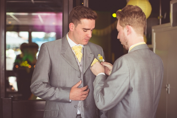 Best man helping groom with buttonhole