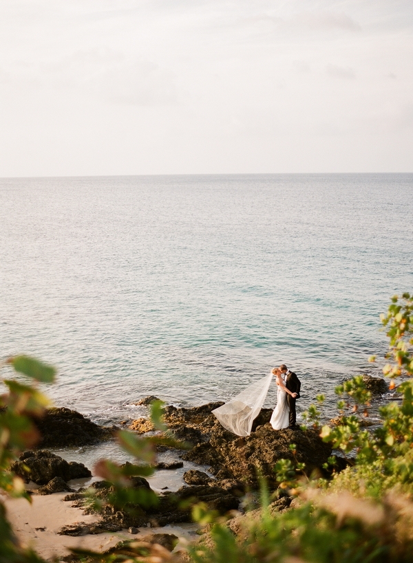 Bride and groom on rocks by sea
