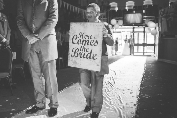 Boy carrying Here Comes the Bride sign
