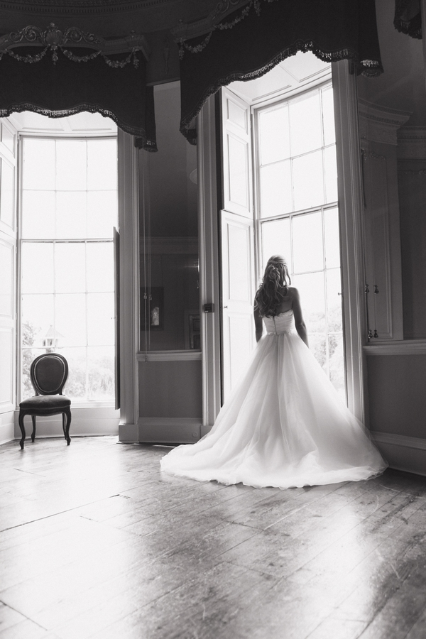 Bride looking out of tall window